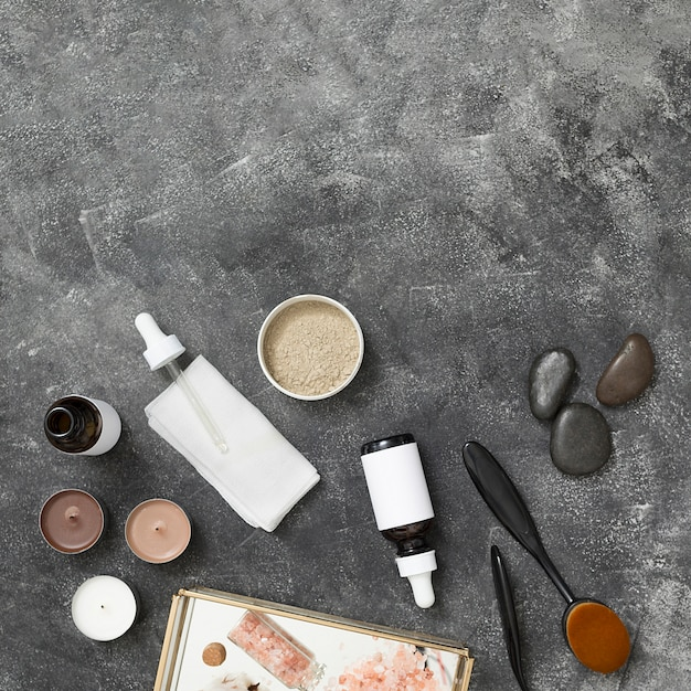 Candles; essential oil bottle; rhassoul clay; la stone; himalayan rock salt on tray against black concrete backdrop Free Photo