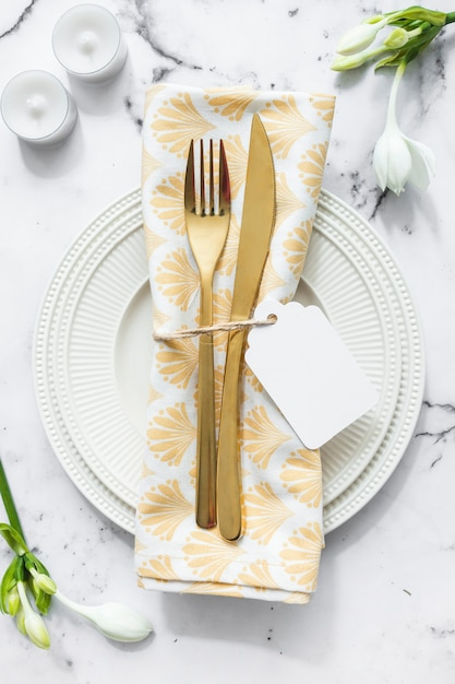 Candles; flower and white plate with folded napkin and cutlery on textured backdrop Free Photo