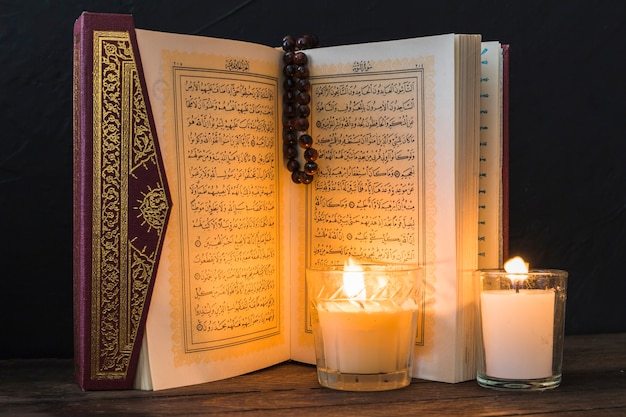 Candles lighting pages of opened quran Photo | Free Download