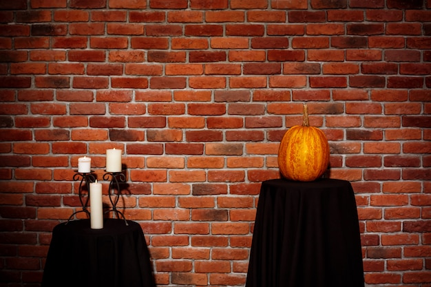Candles and pumpkin on table over brick wall. halloween. copy space. Free Photo