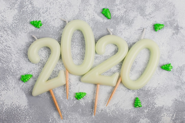 Candles in the shape of numbers 2020 as a symbol of the new year next to christmas shaped sparkle candies on a gray table. top view, flat lay Free Photo