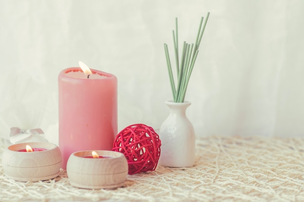 Candles and vase with sticks Free Photo
