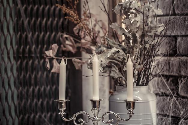 Candeliere con candele e fiori secchi Foto Gratuite