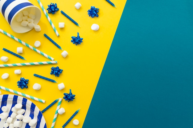 Candy and candles on yellow and blue background Free Photo