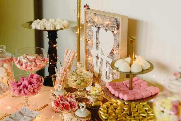 Candy bar beautifully decorated with sweets in a vintage event. Premium Photo