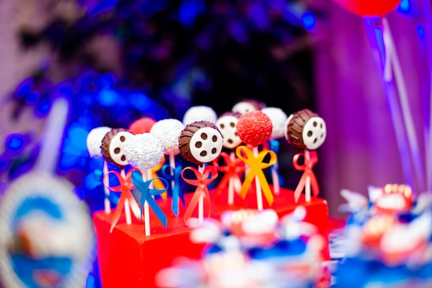 Candy bar on boy's birthday party with a lot of different candies, popcorn, beverages and big cake Premium Photo