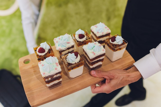 Candy bar. delicious sweet buffet with cupcakes and cake-pops. sweet holiday buffet with cupcakes and other desserts in green, blue and orange tones. Premium Photo