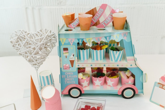 Candy bar shaped like a bus, decorated with pink tones. Premium Photo