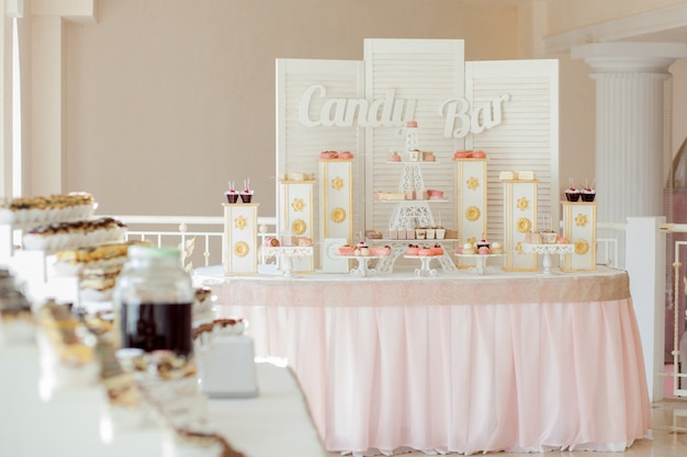Candy bar. sweet holiday buffet with cupcakes and other desserts. Premium Photo