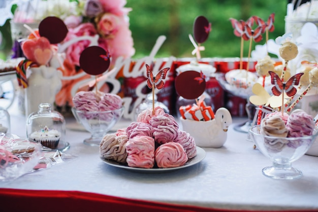 Candy bar with marshmallows and cupcakes decorated with flowers and butterflies Premium Photo