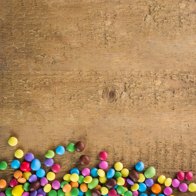 Candy buttons on wooden background.  Free Photo