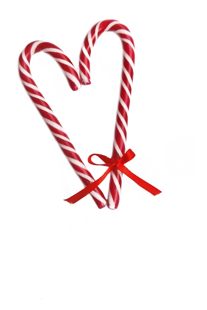 Candy canes forming a heart with a little ribbon on one and isolated on white Premium Photo