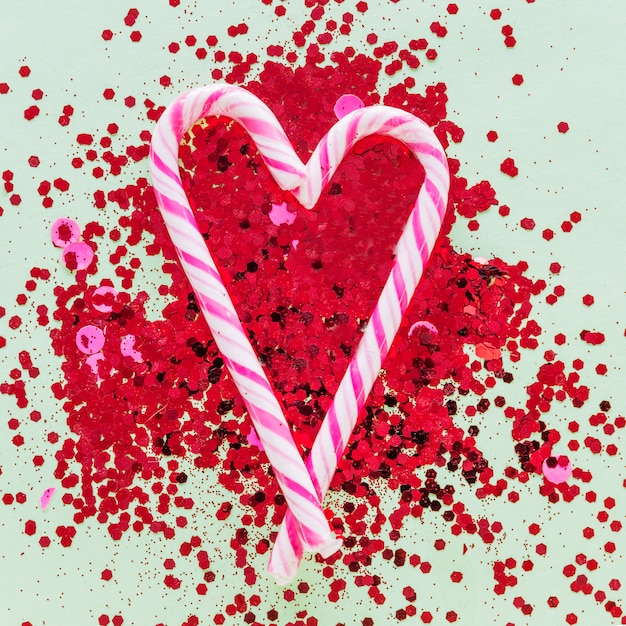 Candy canes in heart shape on spangles Free Photo