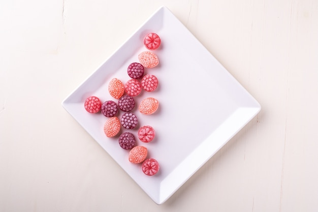 Candy canes sweets in form of juicy berries on white plate on white background isolated, top view Premium Photo
