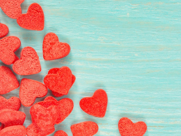 Candy heart confetti on blue wooden background Photo