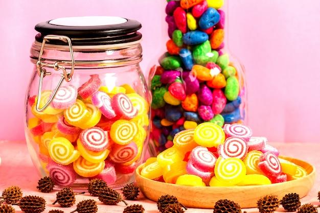 Конфеты в банке на столе на розовом столе Premium Фотографии