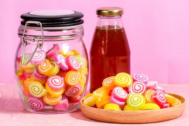 Конфеты с медом в банке на столе на розовом фоне Premium Фотографии