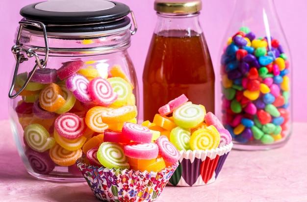 Конфеты с медом в банке на столе на розовом столе Premium Фотографии