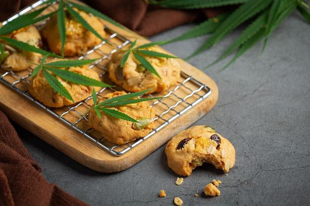 木製のまな板に置かれた大麻クッキーと大麻の葉 無料写真