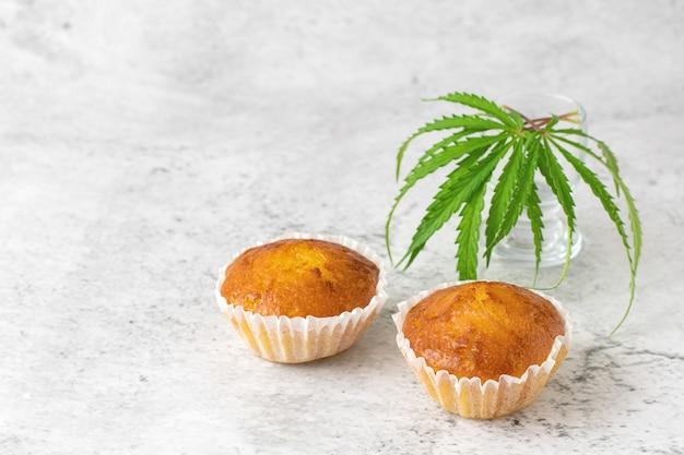 Кексы и листья кексов каннабиса на сером. Premium Фотографии
