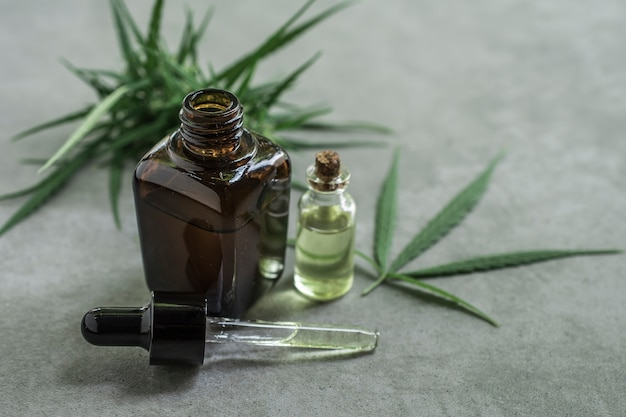 Cannabis essential oil container with cannabis leaves Premium Photo