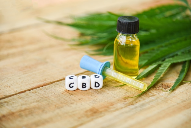 Cannabis oil on bottle products wooden , cbd oil extract from cannabis leaf marijuana leaves Premium Photo