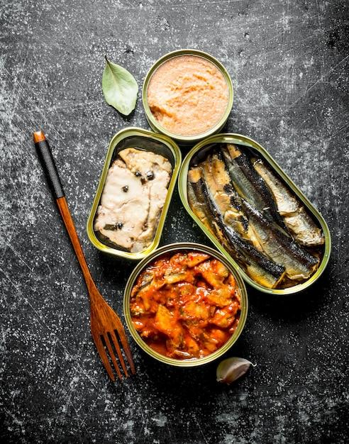 Консервы рыбные в жестяных банках. на темном деревенском фоне Premium Фотографии