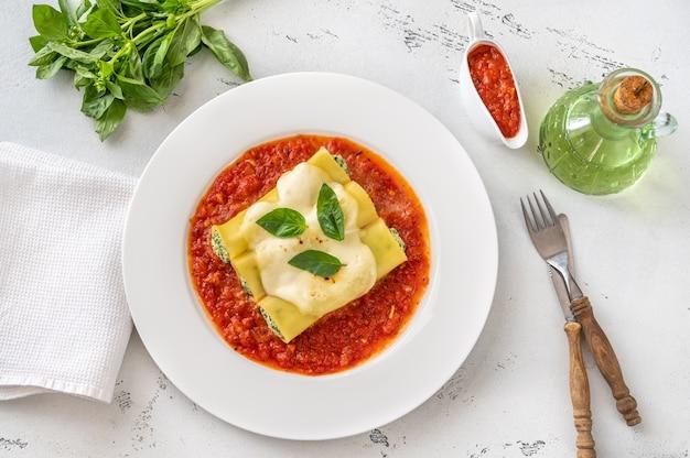 Паста каннеллони с начинкой из рикотты и шпината с томатным соусом Premium Фотографии