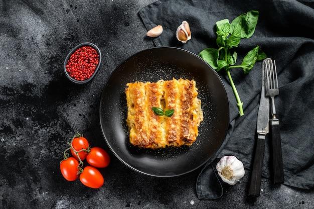 Каннеллони с говядиной и томатным соусом. итальянская домашняя паста. черный фон. вид сверху Premium Фотографии