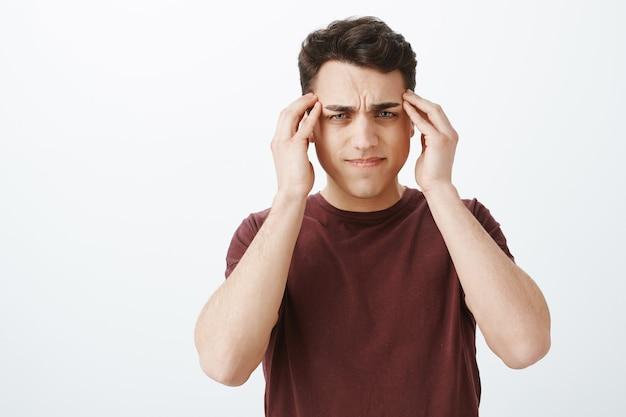 Impossibile concentrarsi sul lavoro causa di mal di testa. ritratto dell'uomo attraente sfocato cupo Foto Gratuite