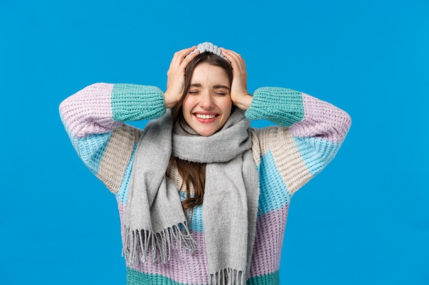 Cant believe dreams do come true, christmas miracle, new year concept. attractive cheerful brunette woman in winter sweater, scarf and jat, close eyes dreamy and smiling, cheering blue Premium Photo