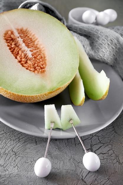 Cantaloupe melone sliced on grey plate Premium Photo
