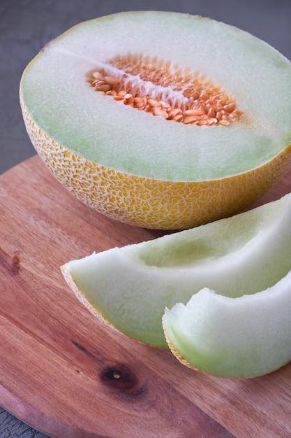 Cantaloupe melone sliced on wooden board on dark Premium Photo
