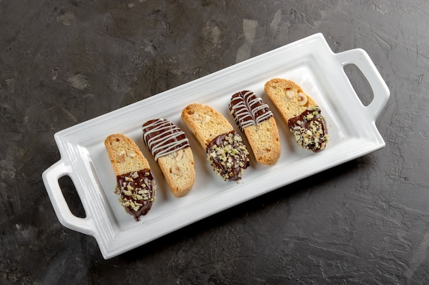 Cantuccini biscuits with chocolate and pistachios on white plate, on stone background. Premium Photo