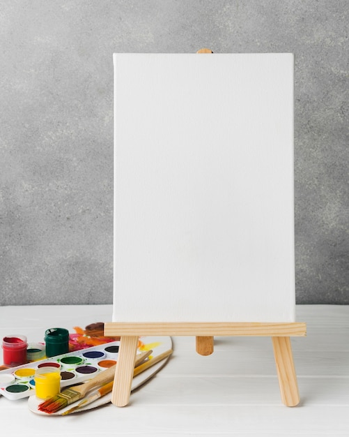 Canvas on easel and color palette Free Photo