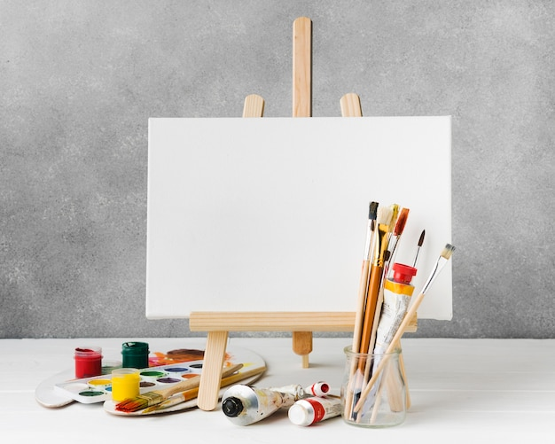 Canvas on easel and watercolour paint front view Free Photo