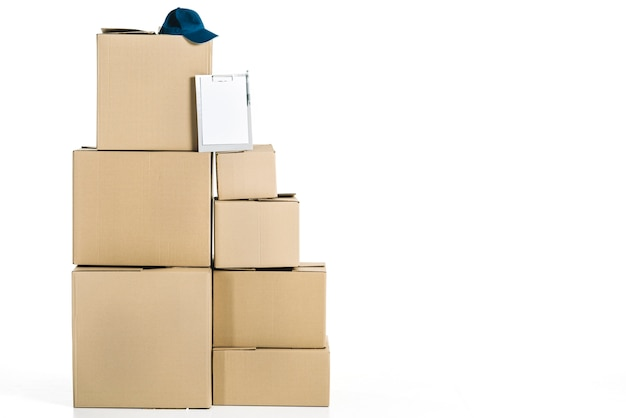 Cap and clipboard on pile of boxes Free Photo