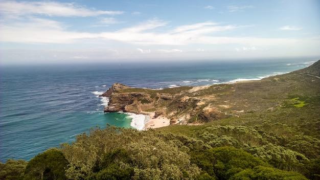 南アフリカの日中の日光の下で海に囲まれた喜望峰 無料写真