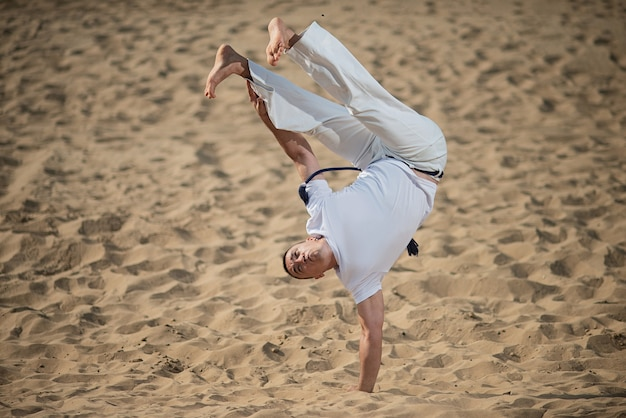 Capoeira dancer posing, performing a handstand Premium Photo