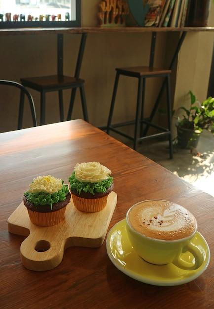 Капучино и два кекса, увенчанные взбитыми сливками в форме цветка, подаются в уютной комнате Premium Фотографии