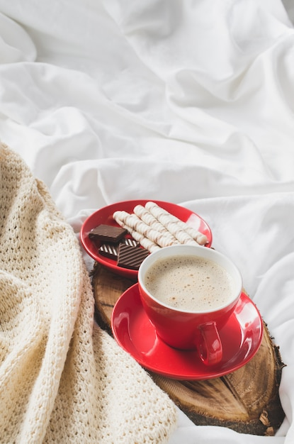 Cappuccino and chocolate on a bed with plaid. Premium Photo