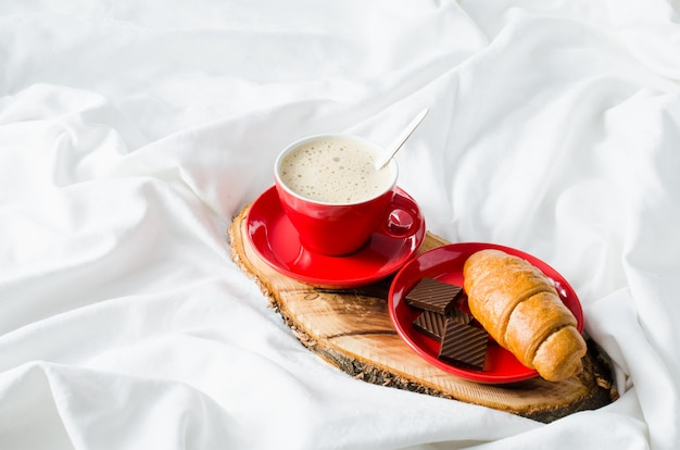 Cappuccino, chocolate and croissant on a bed. Premium Photo