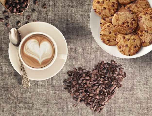 Cappuccino coffee beans in heart shape and home-baked chocolate chip cookies in a coffee house Premium Photo