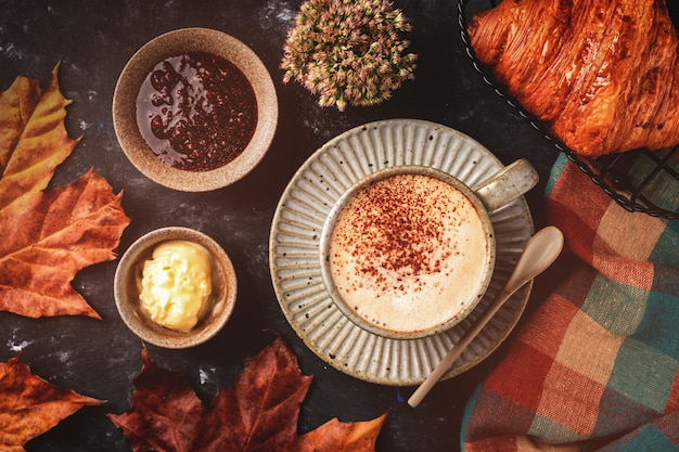 Cappuccino coffee with croissant on the table, autumn breakfast concept, top view Premium Photo