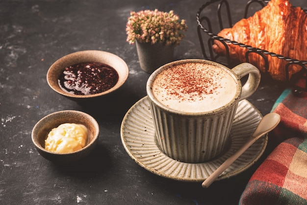 Cappuccino coffee with croissant on the table, breakfast concept, top view Premium Photo