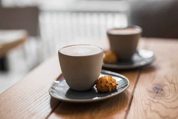 Cappuccino or latte with frothy foam with cookie on wooden table Free Photo