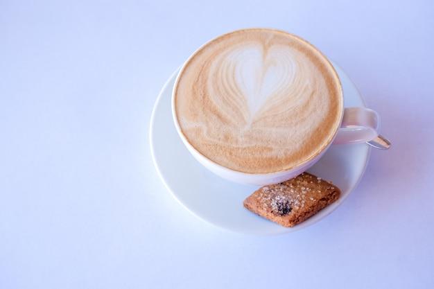 カプチーノまたはラテコーヒーカップに泡立てたミルクとクッキー。アーモンドビスコッティとコーヒーのカップ。ハートデザインのラテ。 Premium写真