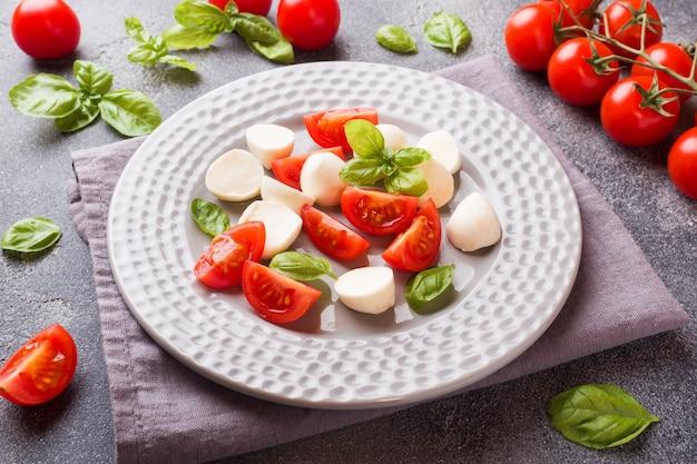 Caprese salad of tomatoes, mozzarella cheese and basil. italian cuisine. Premium Photo