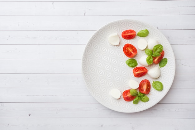 Caprese salad of tomatoes, mozzarella cheese and basil on a white plate. italian cuisine. copy space Premium Photo