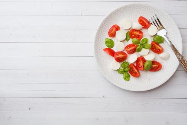Caprese salad of tomatoes, mozzarella cheese and basil on a white plate. italian cuisine. copy space Premium Photo